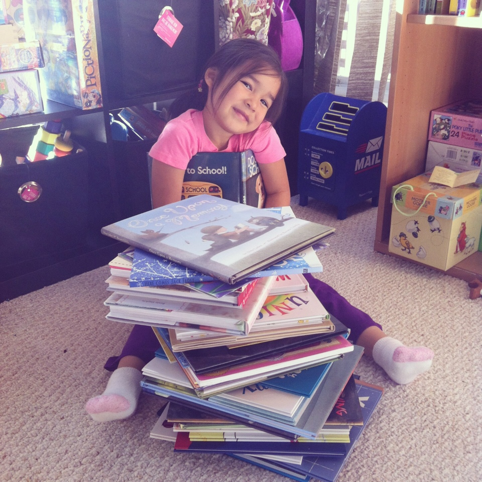 Hello Creative Family kid sitting in front of a pile of books.