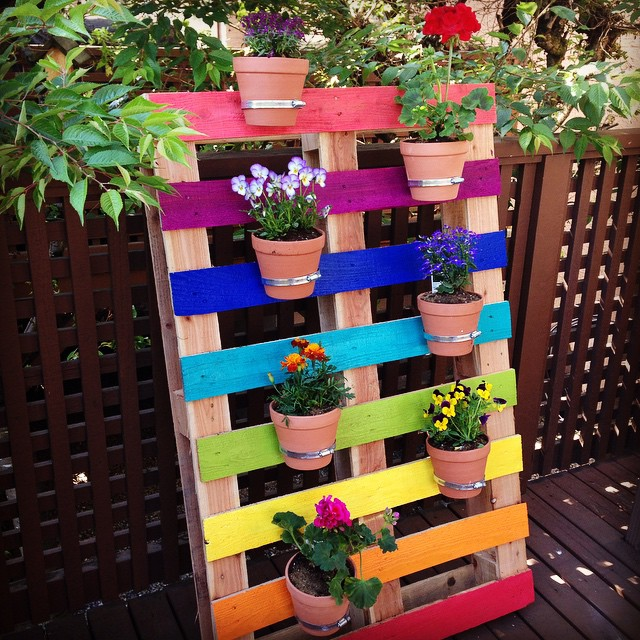 Create a bright and colorful upcycled rainbow pallet planter project with  these simple instructions from Hello. How to Make A DIY Upcycled Rainbow Pallet Flower Garden Planter