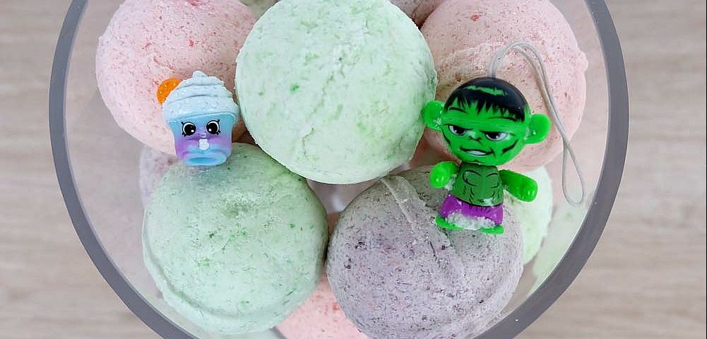 DIY your own handmade bath bombs, with this simple and easy tutorial which includes a video that walks you through step by step. This is a fun craft project for kids and makes bath time fun when kids discover the Shopkins or toy superhero hidden inside! Also makes a wonderful handmade gift for Christmas, Mother's Day, birthdays and other occasions.