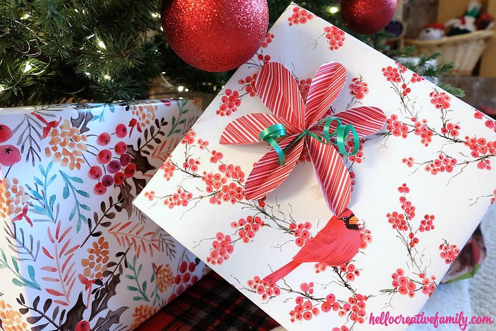 Skip the store bought bows and DIY them instead! Learn How To Make Super Simple DIY Poinsettia Bows For Gift Wrapping. They are so easy and perfect for wrapping Christmas gifts!