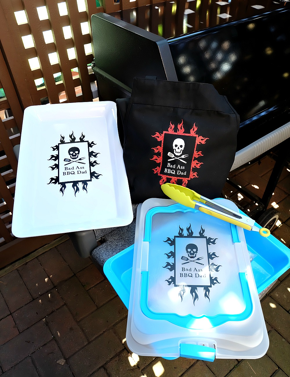 Turn dollar store finds into DIY BBQ Gift Ideas For Dad with this amazing tutorial! Cut the designs with our Cricut Explore, then make a platter and container using vinyl and dishwasher safe mod podge or an apron with heat transfer vinyl. The design says Bad Ass BBQ Dad! Perfect for Father's Day or Christmas!