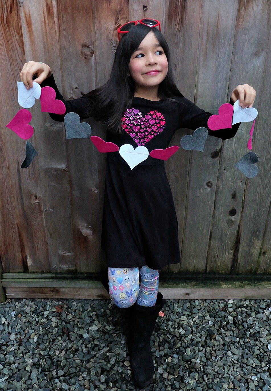 Decorate for Valentine's Day with this easy 5 minute Felt DIY Heart Garland! Customize this project with different colors of felt. So cute not only for decorating the home but also to decorate a classroom or to use as a photo prop! Cut your hearts by hand or with a Cricut Maker. A great first sewing project for kids! #Cricut #craft #ValentinesDay