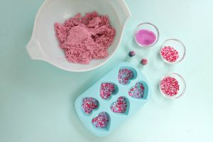 Add sprinkles and candy to the bottom of your silicone molds.