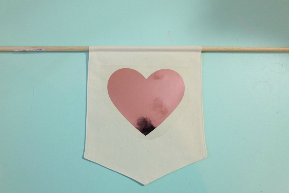 Canvas Wall Banners are so hot right now! Learn how to make a DIY Canvas Wall Banner in just 20 minutes with this easy sewing tutorial! Includes a free Cricut Cut File for making this Love Lives Here Banner on the Cricut Maker or Cricut Explore! Perfect for decorating a family photo wall or as a front door wreath decoration for Valentines Day! #DIY #CricutMade #CricutMaker #Craft #Decor