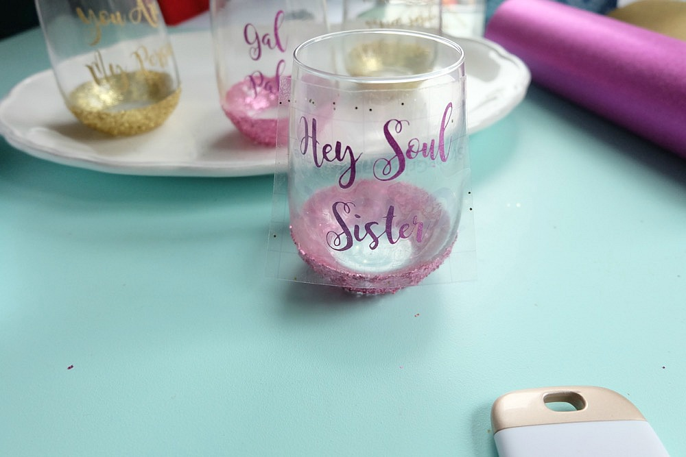 Celebrate Galentine's Day (aka Valentine's Day for with your BFF's) with these super cute DIY Glitter Dipped Wine Glasses. This post shares word art to make 6 different glasses along with an easy step by step tutorial with photos for how to make this project. This would be a great crafternoon project with friends! Use your Cricut to cut the word art. #CricutMade #Crafts #Galentine #DIY #Glitter #Valentine
