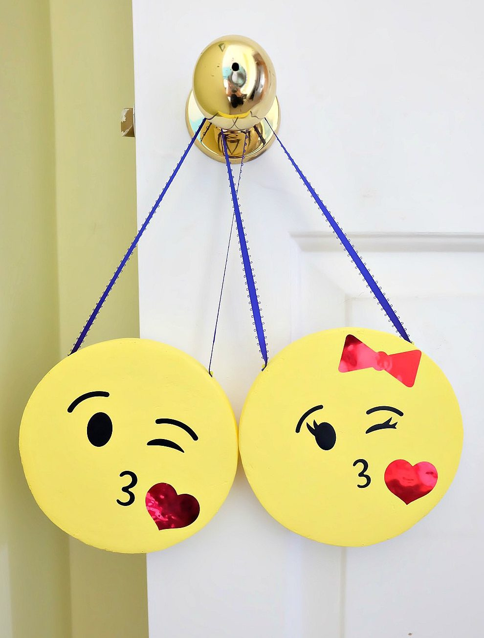 The perfect DIY project to complete an emoji themed kids room or an emoji birthday party! These DIY Emoji Door Hangers are easy to make and a fun kids craft. Use your Cricut to cut the his and her kissy face emoji faces and apply them to painted styrofoam disks. #CricutMade #Emoji #DIY #KidsCrafts