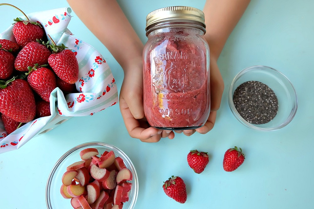 This quick and easy strawberry rhubarb chia jam takes two of my favorite flavors of summer and turns it into one healthy recipe! If you have never made jam before this is the recipe to start with. It uses chia seeds to thicken the jam and takes only 15 minutes start to finish to make! Family friendly, get the kids involved in the kitchen helping to make this delicious treat. Perfect for on bread, mixed with greek yogurt or as an ice cream topper! #Jam #chia #strawberry #rhubarb #recipe