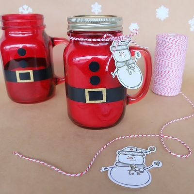 Looking for a quick and easy Christmas gift perfect for neighbors and teacher gifts? These DIY Santa Mason Jars are filled with hot chocolate and take minutes to make! Cut vinyl with scissors or we're also sharing the Cricut cut file for making this project. We're also sharing our hot chocolate mix recipe! Enjoy this handmade gift idea! #Christmas #Santa #Cricut #HandmadeGift #MasonJar