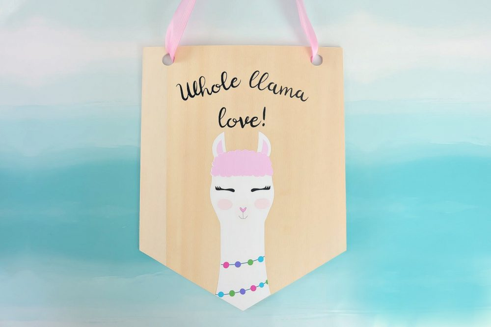 Learn how to cut basswood with your Cricut Maker and make this adorable DIY Llama Wood Wall Hanging featuring acute Print and Cut llama and the quote Whole Llama Love. This craft would make a sweet handmade gift and would be perfect for decorating a girl's bedroom or as a fun front door decoration. Another amazing Cricut Project from Hello Creative Family. #CricutProject #handmade #llama #girlsroom