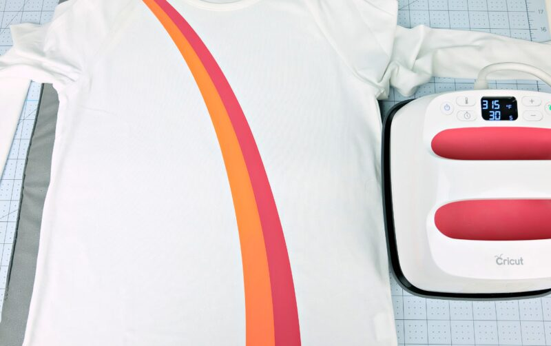 Ue your Cricut EasyPress to apply heat transfer vinyl to create a rainbow shirt.