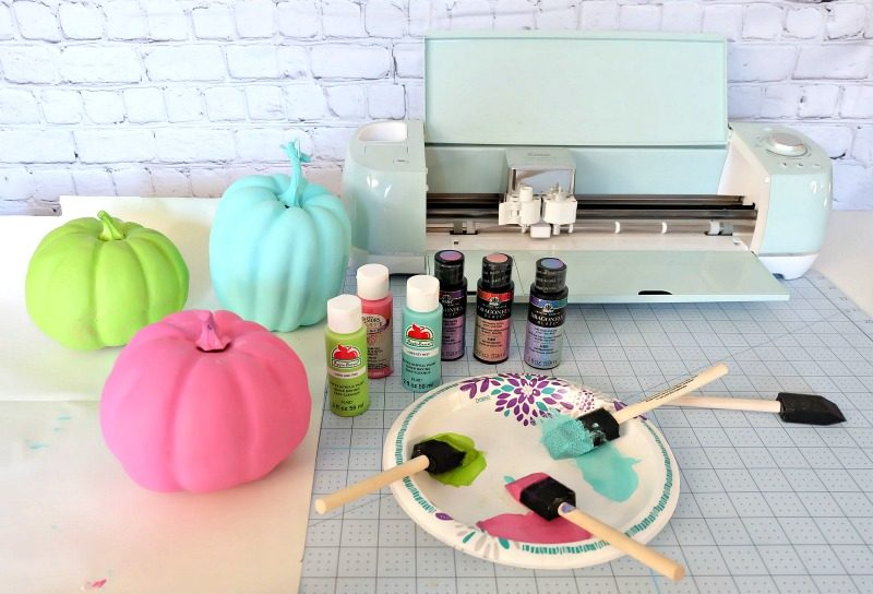 Add some flare to dollar store craft pumpkins with our easy painted pumpkins tutorial! With a bit of paint and some vinyl decals you cut with your Cricut this project makes a fun family friendly Halloween craft! #DIYHalloween #CricutCreated #Cricut #CraftPumpkins