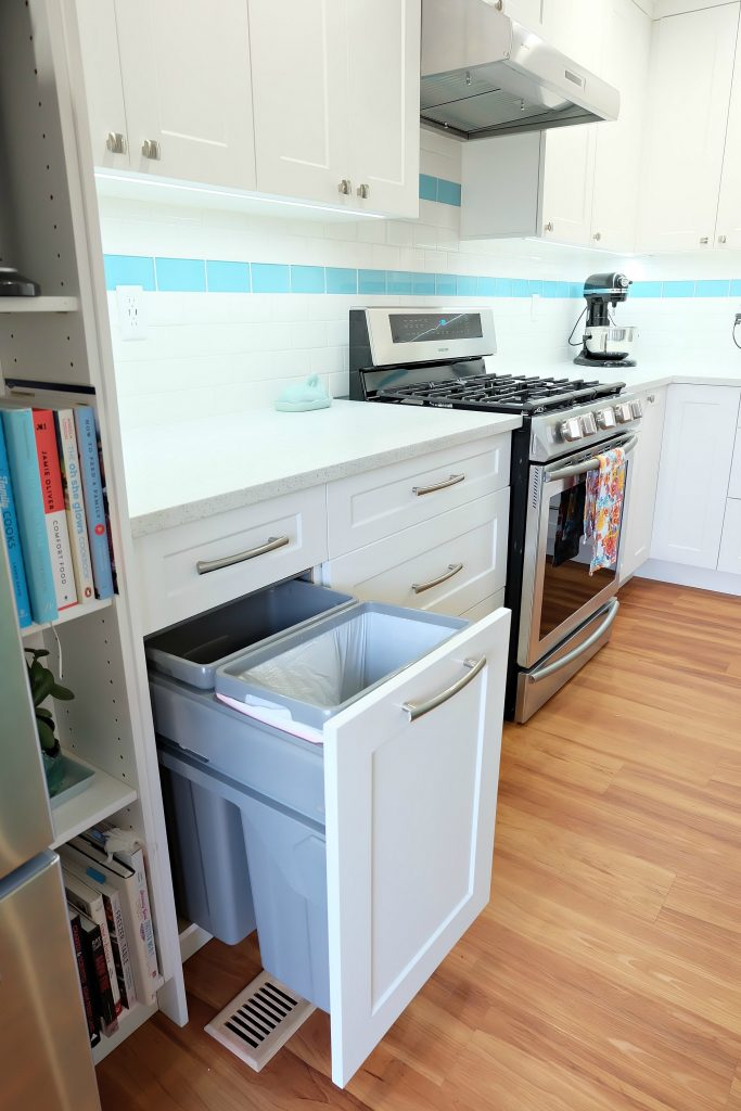 Finding the perfect garbage and recycling center for your family's needs is such an important consideration to make when doing a kitchen remodel. This DIY teal kitchen remodel includes a colorful aqua island and other smart features. Also check out her 20 Tips for a Smooth Kitchen Renovation! #Sponsored #Turquoise #Kitchen #Aqua #KitchenRemodel #kitchenrenovation