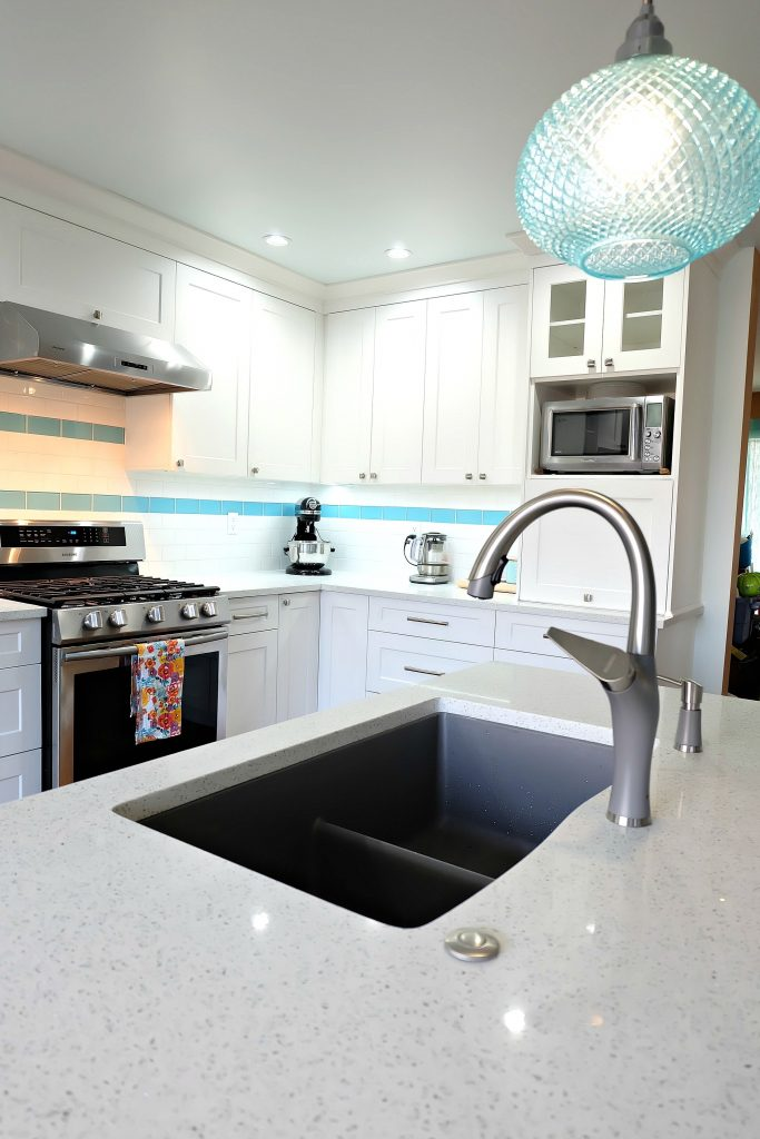 Blanco's Silgranit Diamond U 2 Low Divide Sink and Artona Kitchen Faucet are a great way to add a pop of neutral grey to a bright aqua kitchen space! This DIY turquoise kitchen remodel includes a colorful island and other smart features. #Sponsored #Turquoise #Kitchen #Aqua #KitchenRemodel #kitchenrenovation