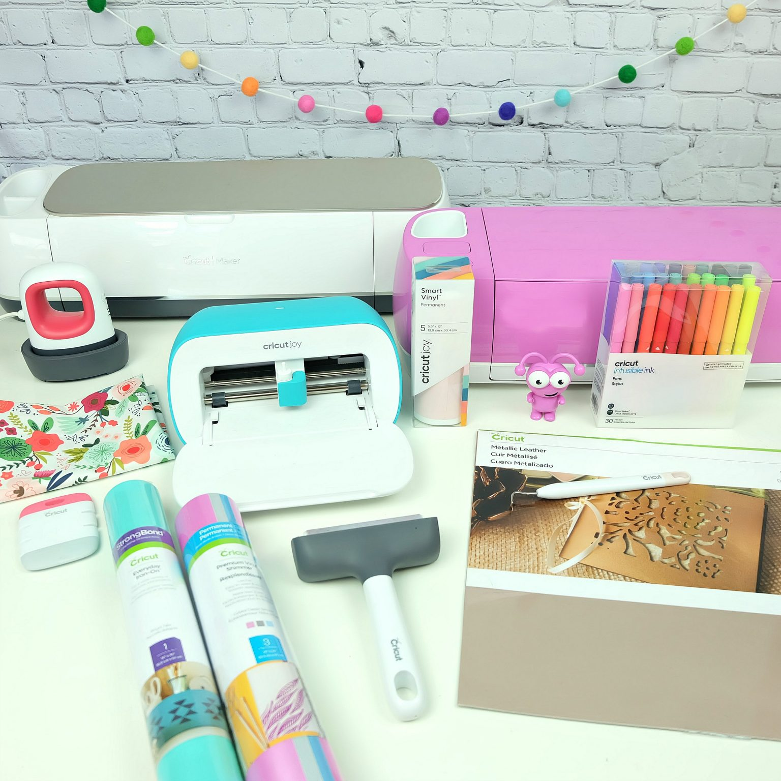 Craft table set up with Cricut Maker, Cricut Explore Air 2 Cricut Joy and Cricut craft supplies.
