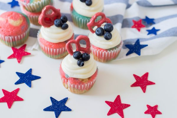 Celebrate the Fourth of July with this Patriotic Cupcakes Recipe! With red, white and blue swirls, buttercream frosting, hand dipped candy coated pretzels and blueberries, this is a fun Fourth of July Cupcake decorating idea! Great for other patriotic holidays too! Who doesnt love red, white and blue food ideas! #Cupcakes #FourthOfJuly #Patriotic #Baking #CupcakeDecorating #Recipe #CupcakeRecipe #RedWhiteAndBlue #PatrioticFood