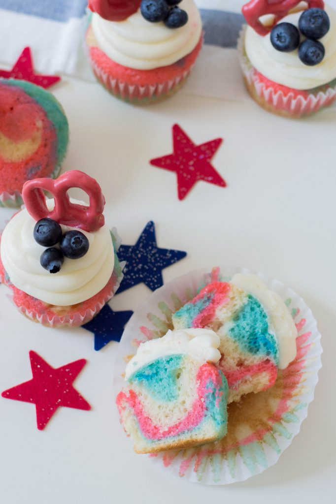 Celebrate the Fourth of July with this Patriotic Cupcakes Recipe! With red, white and blue swirls, buttercream frosting, hand dipped candy coated pretzels and blueberries, this is a fun Fourth of July Cupcake decorating idea! Great for other patriotic holidays too! Who doesn't love red, white and blue food ideas! #Cupcakes #FourthOfJuly #Patriotic #Baking #CupcakeDecorating #Recipe #CupcakeRecipe #RedWhiteAndBlue #PatrioticFood