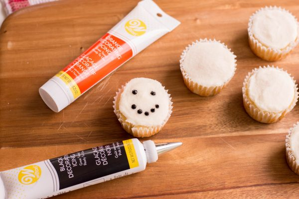 Adding snowman faces to cupcakes using black and orange decorating icing.
