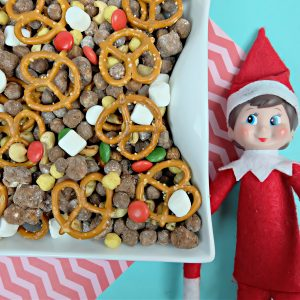 Yummy Chocolate Peanut Butter Cereal Christmas Snack Mix Next To Elf On The Shelf.