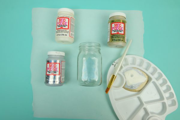 Different types of Mod Podge Mega Glitter with a mason jar, painters palette and paint brush.