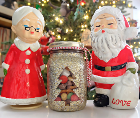Finished DIY Glitter Mason Jar filled with cereal snack mix, between Mr. & Mrs Claus