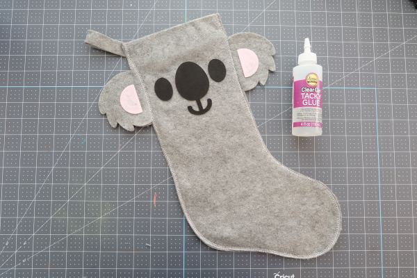 Use fabric glue to glue the face onto your stocking.