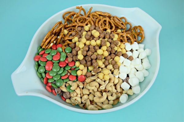 Adding pretzels, M&M's, cashews and marshmallows to peanut butter chocolate snack mix.