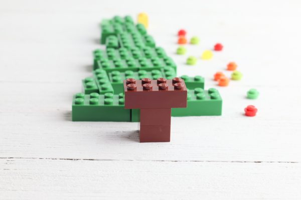 Make the trunk by stacking 2 2x2 brown bricks with one 2x4 brown brick on top.