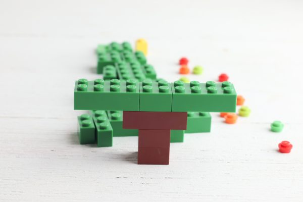 Add one 2x2 green brick to the center of the trunk and two 2x4 green bricks on each side.