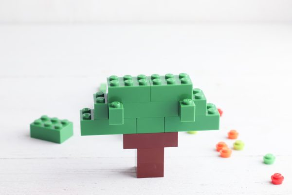 Place two 2x3 green bricks on the next row.