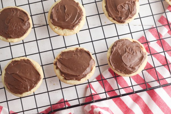 Spread an even layer of chocolate icing over the top of each cookie.