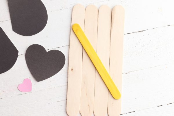 Lay the large popsicle sticks on a flat surface and glue the small stick to the back to hold them in place.