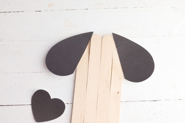 Glue the two halves of the large heart to each side of the popsicle sticks to make ears.