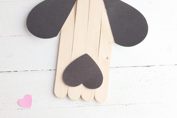 Turn the medium sized heart upside down and glue it to bottom of the popsicle sticks.