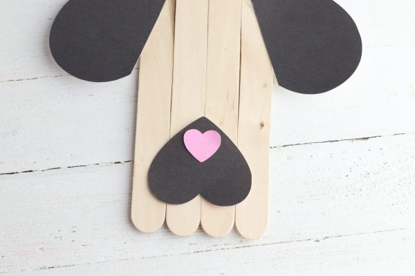 Glue the small heart to the tip of the black heart as the dog's nose.