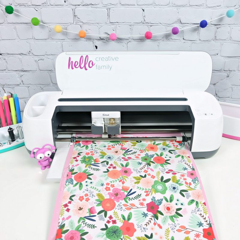 Cricut Maker loaded with a fabric mat with pretty floral fabric. A Cricut cutie sits next to the Cricut Maker.
