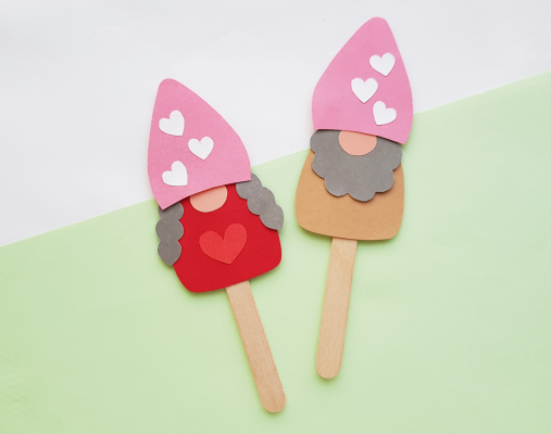 Attach the paper gnomes on popsicle sticks to complete the craft. Optional add an extra heart on the gnomes' tummies.