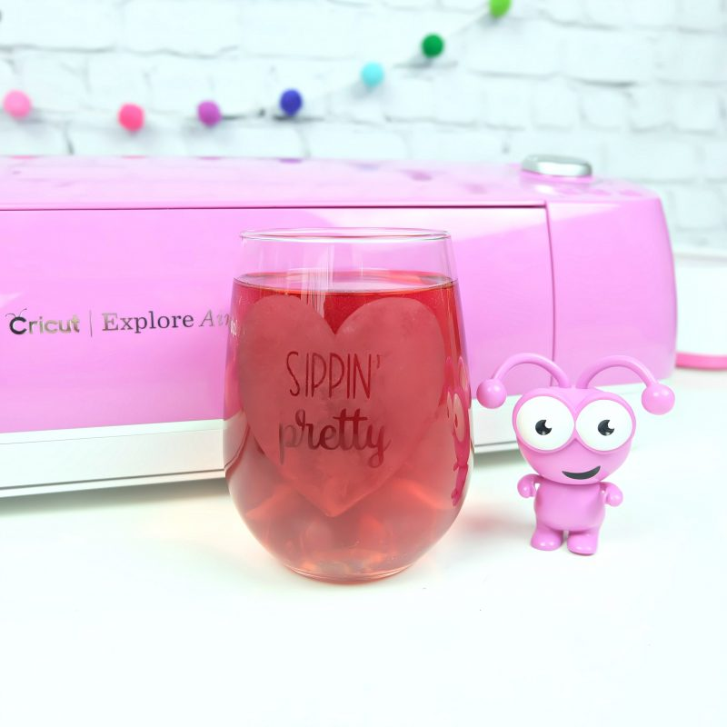 A pink Cricut Cutie stands in front of a fuchsia Cricut Explore Air 2 and a white brick wall with a felt pom pom garland. He stands next to a wine tumbler filled with pink liquid that has Sippin' Pretty etched in it. Project and cut file from the Book The Unofficial Book of Cricut Crafts