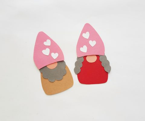 Glue the paper hats onto the top of the gnomes' bodies, slightly overlapping the nose on the top side.
