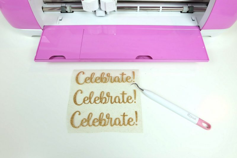 Gold Glitter HTV with the words celebrate and a weeding tool.