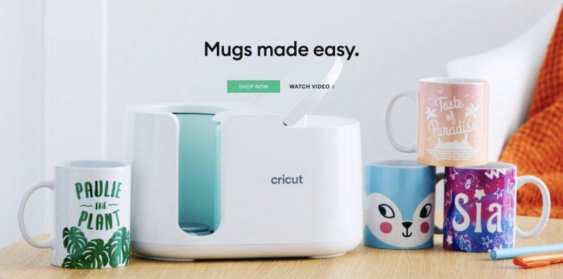 Cricut Mug Press on a table with DIY mugs