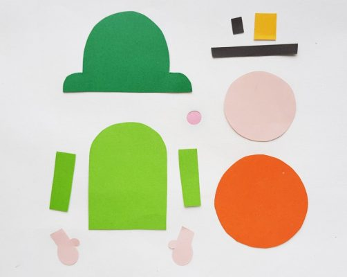 Print out the leprechaun bookmark template and trace the pieces onto construction paper. Trace the head, nose and hand patterns on light pink paper. Trace the hat, body and sleeve patterns on green paper. Trace the beard on orange, the strip and the small square on black paper and trace the medium square on yellow paper. Cut out each of the traced papers.