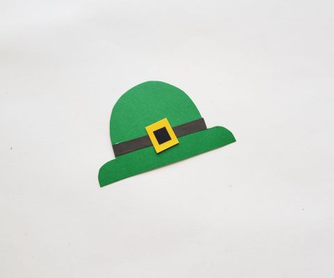 Attach the black strip near the bottom side of the hat cutout. Glue the small black square inside the yellow square and then glue the squares on the middle of the black strip to complete the hat craft.
