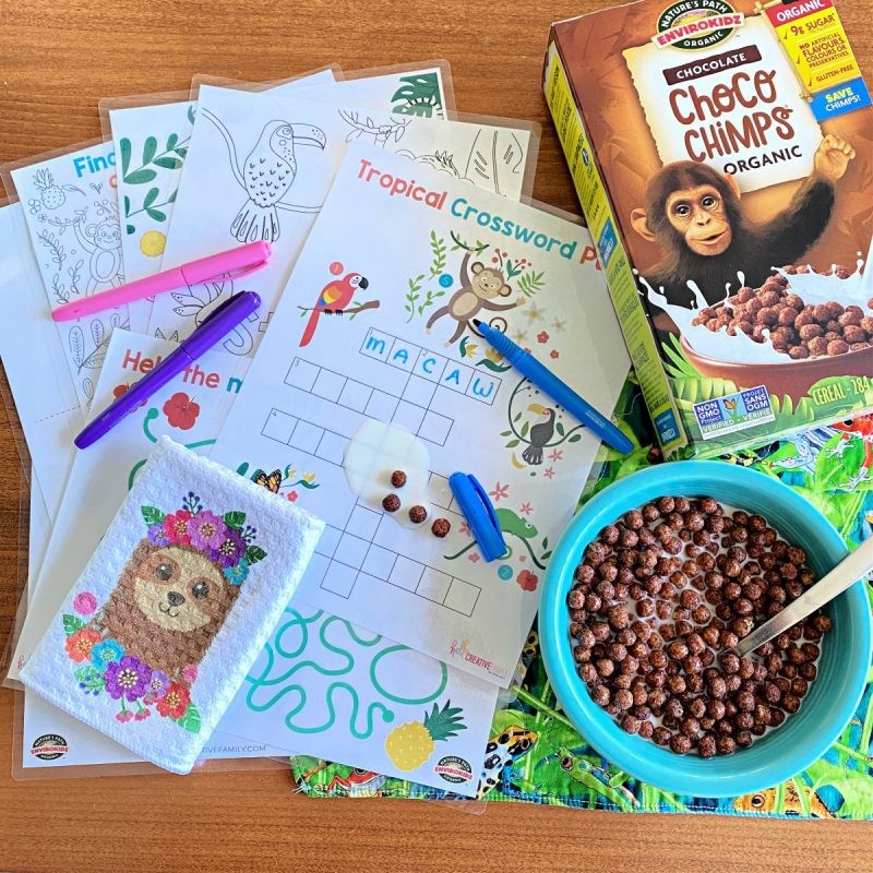 Laminated Rainforest Activity Sheet Printable Bundle with a bowl of ChocoChimps EnviroKidz Cereal! Milk and cereal is spilled on the laminated pages.