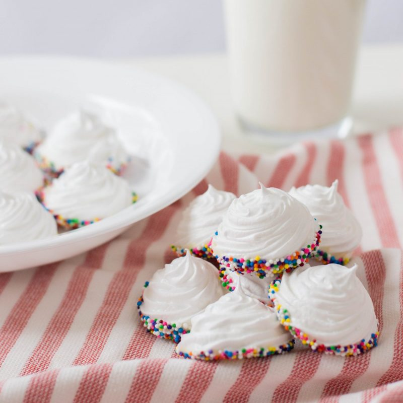 Get ready for a simple and easy birthday dessert idea that packs a ton of pizzaz with this birthday meringue cookies recipe! These beautiful white peaked meringues are dipped in white chocolate and covered in rainbow sprinkles for a fun and festive sweet birthday treat! This recipe uses just 5 ingredients and are just as cute as can be!