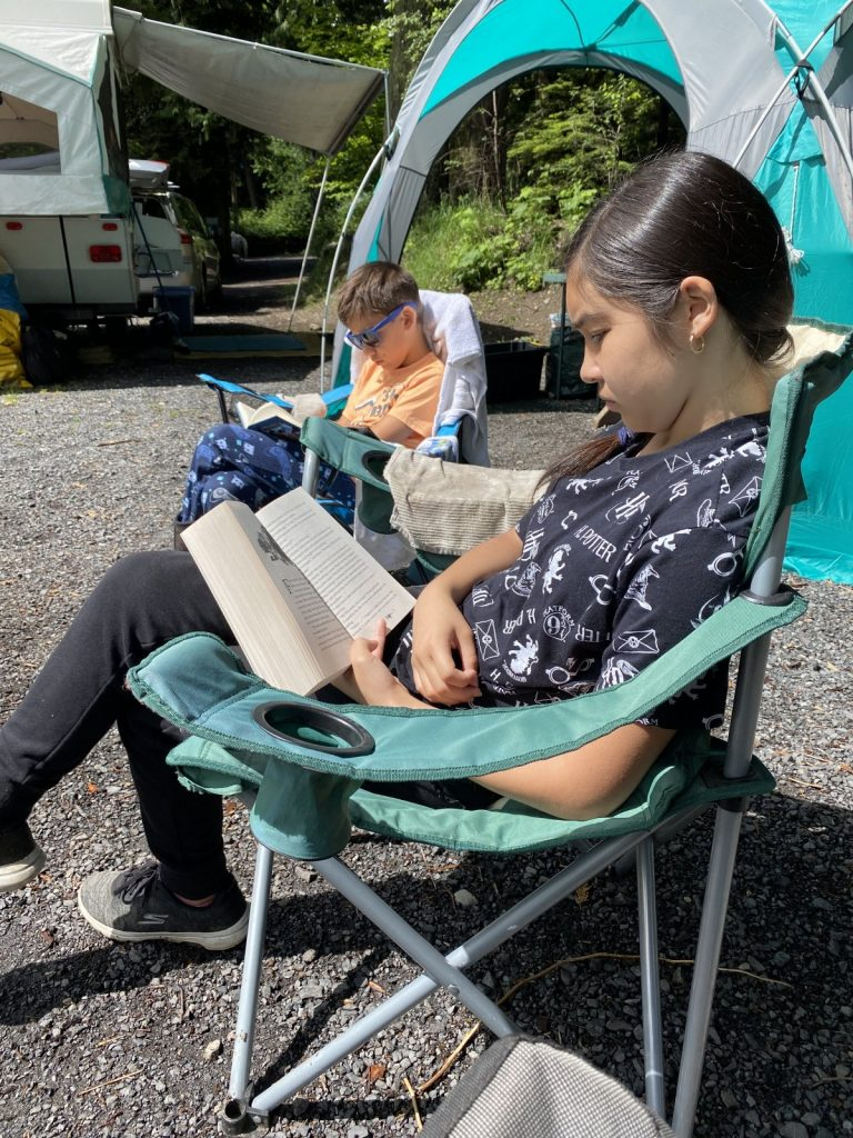 Hello Creative Family kids reading books while camping.