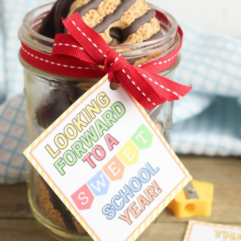 Sweet handmade teacher gift. Mason jar with cookies with an pretty colorful gift tag that says Looking Forward To A Sweet School Year.