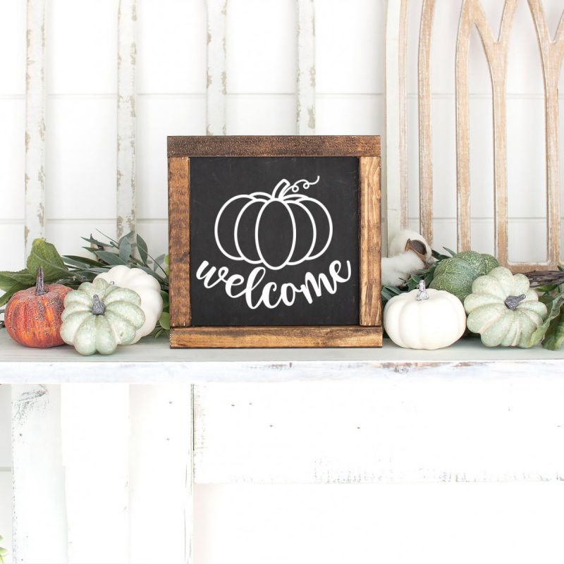 DIY Wood sign on a mantle with the word welcome and a hand drawn pumpkin.