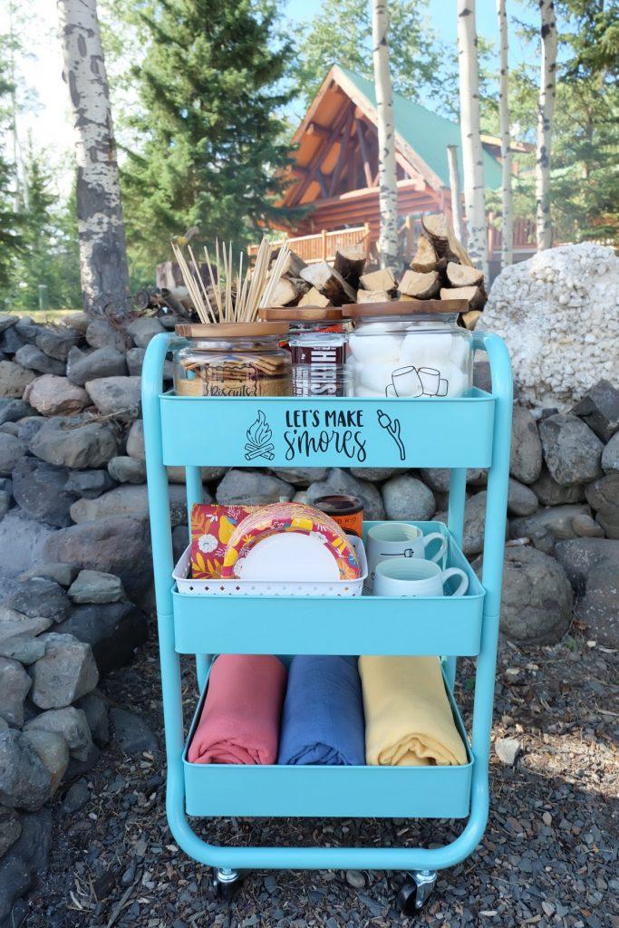 DIY Smores Cart in front of beautiful log cabin