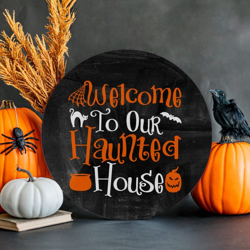 DIY Welcome To Our Haunted House Sign surrounded by pumpkins and Halloween decor.